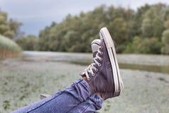 Piernas con las zapatillas de deporte en el lago Imagen de archivo