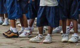Piernas con las zapatillas de deporte y los pantalones del uniforme escolar del africano de los alumnos pre, Matadi, Congo, Áfric fotos de archivo