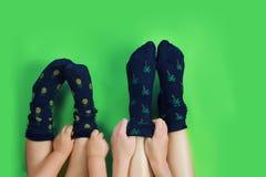 Piernas con los calcetines azules lindos en fondo verde Fotos de archivo libres de regalías
