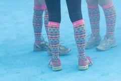 Piernas con los calcetines coloridos y polvo azul del color en la tierra Fotografía de archivo libre de regalías