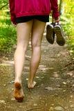 Piernas con los pies desnudos que caminan a lo largo de la trayectoria de bosque Fotos de archivo libres de regalías
