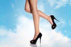 Piernas con los zapatos de tacón alto negros en un cielo Imagenes de archivo