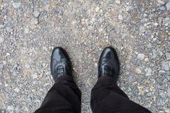 Piernas con los zapatos negros en los guijarros Fotos de archivo libres de regalías