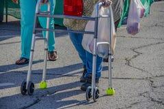 Piernas cosechadas de la mujer con el caminante en la calle del asfalto con el bolso de la producción en el mercado de los granje imagen de archivo