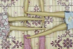 Piernas cruzadas de cuatro muñecas que mienten en el piso fotografía de archivo libre de regalías