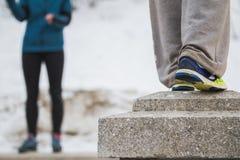 Piernas de adolescentes en el entrenamiento del parkour - las zapatillas de deporte en invierno parquean Fotos de archivo
