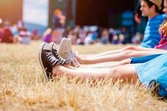 Piernas de adolescentes, festival de música, delante de la etapa Fotos de archivo libres de regalías