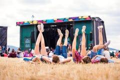 Piernas de adolescentes, festival de música, delante de la etapa Foto de archivo libre de regalías