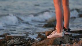 Piernas de dos mujeres jovenes que se colocan en fila en la orilla de mar rocosa almacen de video