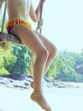 Piernas de la chica joven en la playa Foto de archivo libre de regalías