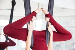 Piernas de la deportista que hacen ejercicio aéreo de la yoga Foto de archivo libre de regalías