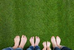 Piernas de la familia que se colocan en hierba verde Fotografía de archivo