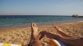 Piernas de la gente de los pares que miente en el ocioso de Sun de la playa cerca del Mar Rojo almacen de video