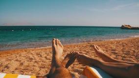 Piernas de la gente de los pares que miente en el ocioso de Sun de la playa cerca del Mar Rojo metrajes