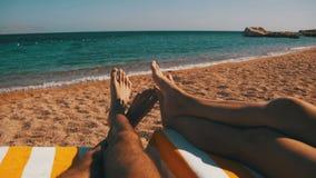 Piernas de la gente de los pares que miente en el ocioso de Sun de la playa cerca del Mar Rojo almacen de metraje de vídeo