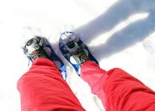 Piernas de la gente mientras que snowshoeing en las montañas Imagen de archivo