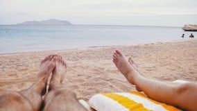 Piernas de la gente que miente en el ocioso de Sun de la playa cerca del mar metrajes