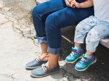 Piernas de la mamá y de la hija que se sientan en la silla en el parque Fa feliz foto de archivo