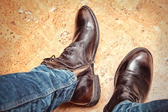 Piernas de la moda de los hombres en tejanos y botas de cuero marrones Imágenes de archivo libres de regalías