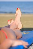 Piernas de la muchacha agradable en la playa de la arena Fotografía de archivo