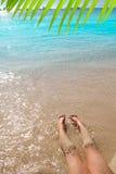 Piernas de la muchacha de los niños en orilla de la arena de la playa Imagenes de archivo