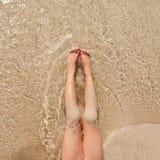 Piernas de la muchacha de los niños en orilla de la arena de la playa Fotografía de archivo