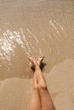 Piernas de la muchacha de los niños en orilla de la arena de la playa Foto de archivo