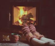 Piernas de la muchacha en calcetines cerca de la chimenea con una taza de té Fotos de archivo