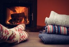 Piernas de la muchacha en calcetines hechos punto cerca de la chimenea Imagen de archivo libre de regalías