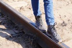 Piernas de la muchacha en las pistas ferroviarias Fotografía de archivo