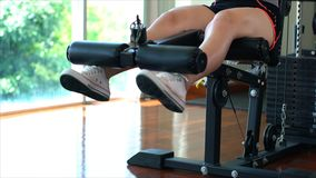 Piernas de la muchacha joven del deporte que hace rizos de pierna asentados en la máquina en la GY imagen de archivo libre de regalías