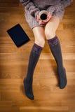 Piernas de la mujer con café Imagen de archivo libre de regalías