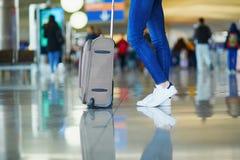 Piernas de la mujer con equipaje en aeropuerto internacional fotos de archivo libres de regalías