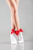 Piernas de la mujer con los calcetines y las cintas rojas Fotos de archivo libres de regalías