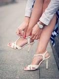 Piernas de la mujer con sandalias del blanco de los tacones altos Fotos de archivo