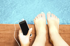Piernas de la mujer con smartphone de la pantalla en blanco en la piscina - liste Fotos de archivo libres de regalías