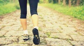 Piernas de la mujer de la aptitud que caminan en rastro Fotografía de archivo