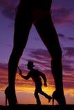Piernas de la mujer del arma del funcionamiento del vaquero de la silueta Imagen de archivo libre de regalías