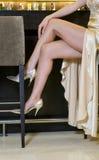 Piernas de la mujer elegante que se sientan en una barra de lujo Imágenes de archivo libres de regalías