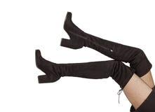 Piernas de la mujer en botas negras del ante en el fondo blanco Fotos de archivo libres de regalías
