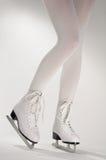 Piernas de la mujer en los patines de hielo blancos Imágenes de archivo libres de regalías