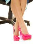 Piernas de la mujer en talones rosados y pies que se sientan del vestido azul cruzados Imagen de archivo