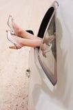 Piernas de la mujer en ventana de coche Imagen de archivo libre de regalías