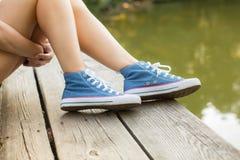 Piernas de la mujer en zapatillas de deporte en una madera Foto de archivo libre de regalías