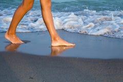 Piernas de la mujer joven en la playa en la puesta del sol Fotos de archivo