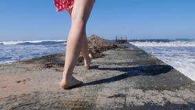 Piernas de la mujer joven que caminan en el embarcadero descalzo con las ondas fuertes que golpean contra el embarcadero metrajes