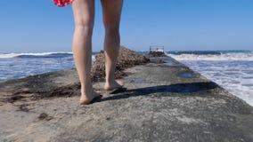 Piernas de la mujer joven que caminan en el embarcadero descalzo con las ondas fuertes que golpean contra el embarcadero C?mara l almacen de metraje de vídeo