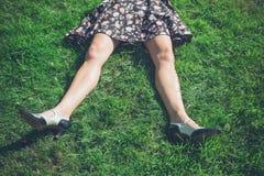 Piernas de la mujer joven que mienten en hierba en campo Fotos de archivo libres de regalías