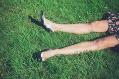 Piernas de la mujer joven que mienten en hierba en campo Foto de archivo libre de regalías