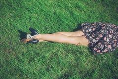 Piernas de la mujer joven que mienten en hierba en campo Imagen de archivo